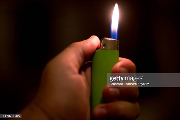 close-up of hand holding cigarette lighter on black background - cigarette lighter stock pictures, royalty-free photos & images