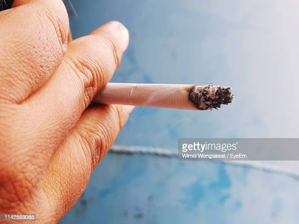 close-up of hand holding cigarette - wimol wongsawat stock photos and pictures