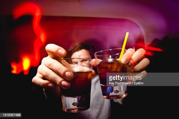 close-up of hand holding cocktail glasses - honour stock pictures, royalty-free photos & images