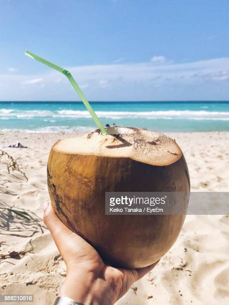 Close-Up Of Hand Holding Coconut Water At Beach Against Sky