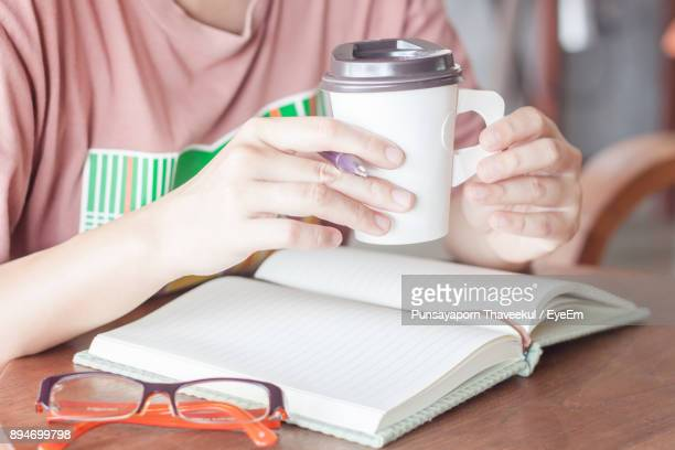Close-Up Of Hand Holding Coffee Cup Over Book