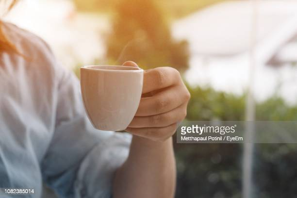 close-up of hand holding coffee cup - metthapaul stock photos and pictures