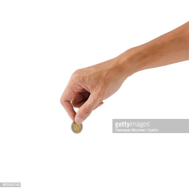 close-up of hand holding coin against white background - coin stock pictures, royalty-free photos & images