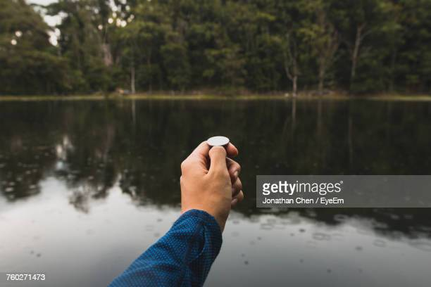 close-up of hand holding coin - flipping a coin stock pictures, royalty-free photos & images