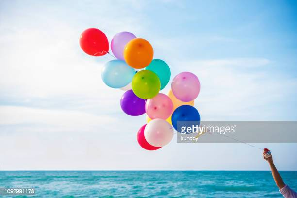 Closeup of hand holding colorful balloon on the beach with blue sky background.
