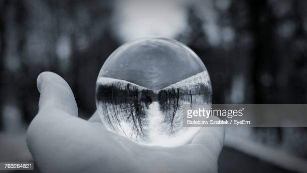 Close-Up Of Hand Holding Crystal Ball With Reflection Of Trees During Winter