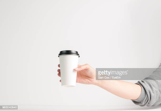 close-up of hand holding disposable cup against white background - disposable cup stock pictures, royalty-free photos & images
