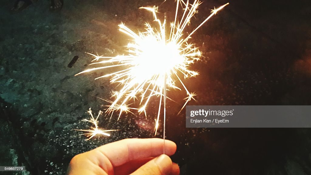 close up of hand holding diwali cracker against blurred background stock photo