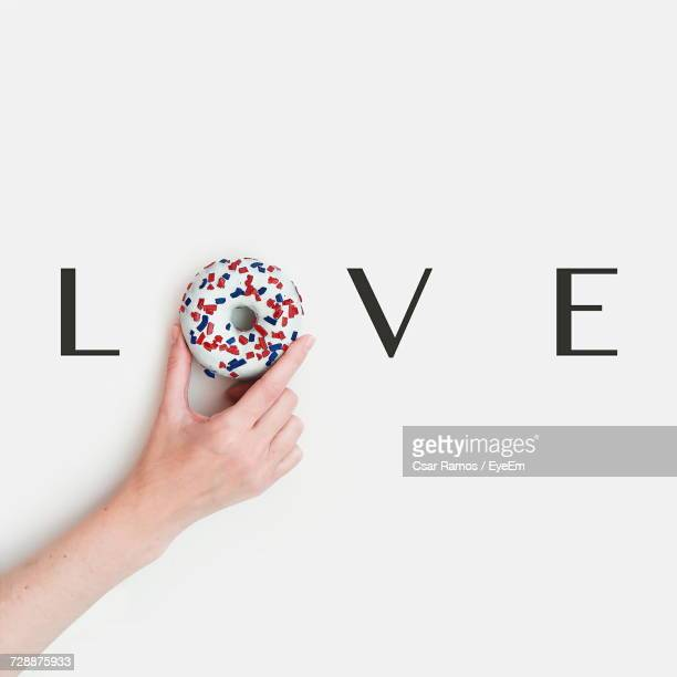 Close-Up Of Hand Holding Donut On White Background