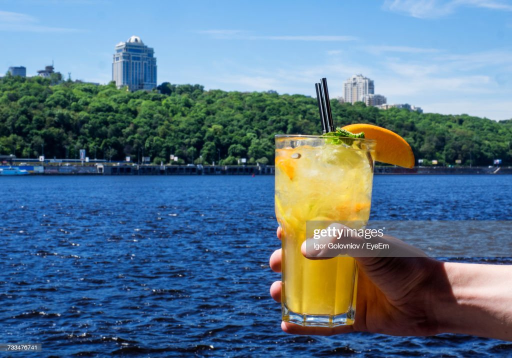 Close-Up Of Hand Holding Drink By Sea Against Sky : Stock Photo