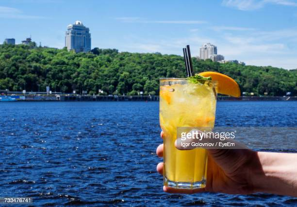 close-up of hand holding drink by sea against sky - igor golovniov stock pictures, royalty-free photos & images
