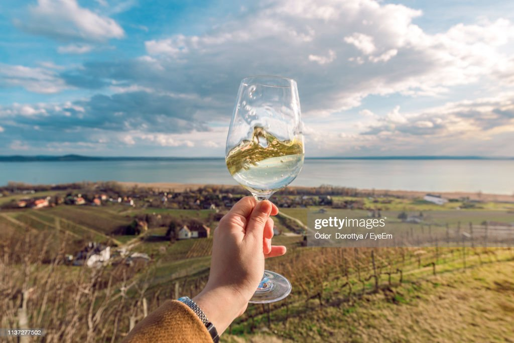 Close-Up Of Hand Holding Drink In Glass Against Sky : Stock Photo