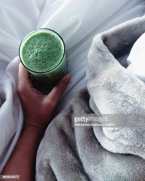 Close-Up Of Hand Holding Drink On Bed