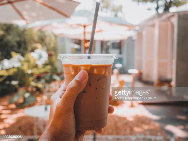 close-up of hand holding drink - apisit hiranpornpan stock pictures, royalty-free photos & images