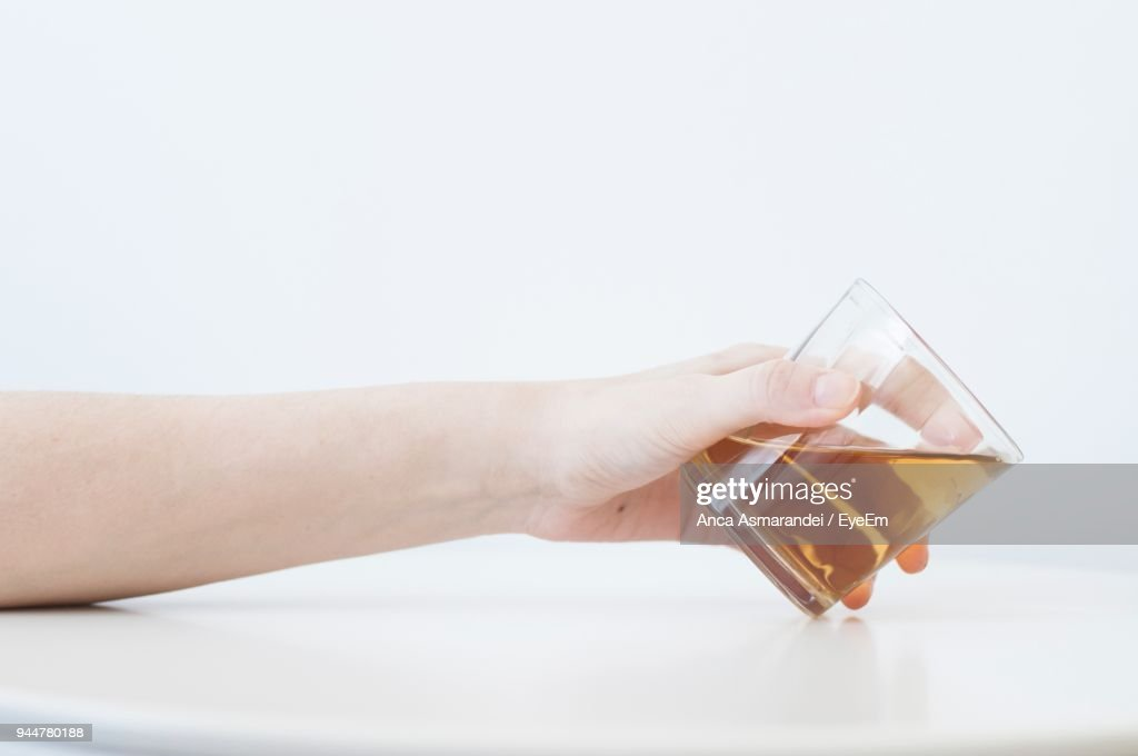 Close-Up Of Hand Holding Drinking Glass Over White Background : Stock Photo