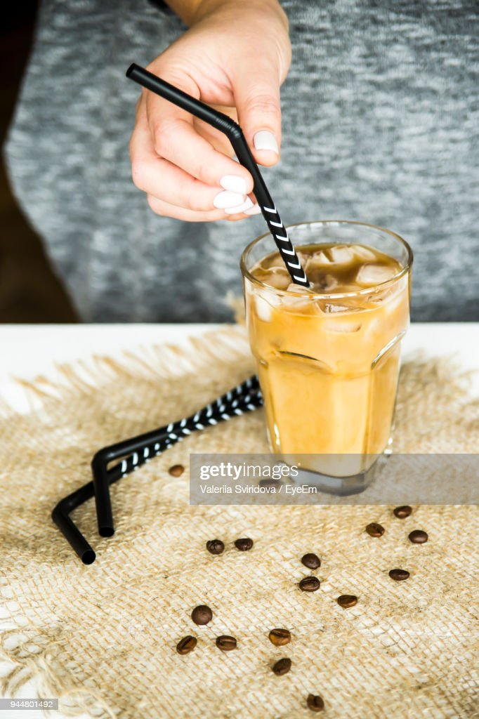 Close-Up Of Hand Holding Drinking Straw In Cold Coffee On Table : Stock Photo
