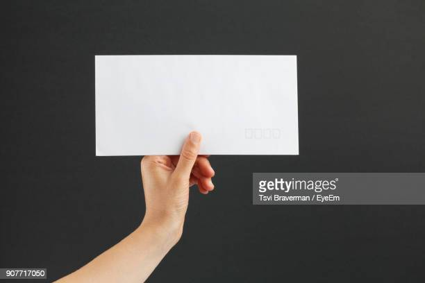 close-up of hand holding envelope over table - 封筒 ストックフォトと画像