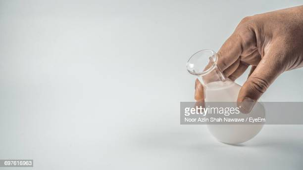 Close-Up Of Hand Holding Erlenmeyer Flask