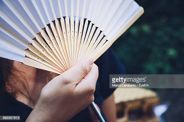 Close-Up Of Hand Holding Fan