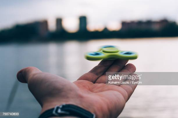 Close-Up Of Hand Holding Fidget Spinner