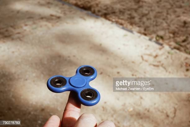 Close-Up Of Hand Holding Fidget Spinning Gadget