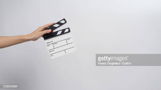 close-up of hand holding film slate against white background - film director stock pictures, royalty-free photos & images