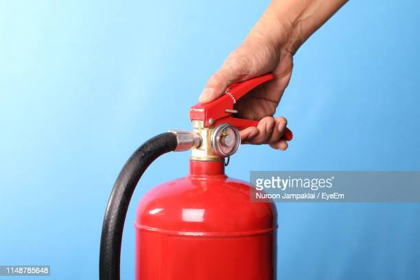close-up of hand holding fire extinguisher against blue background - 消火器 ストックフォトと画像