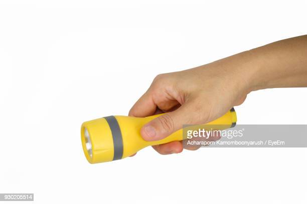 close-up of hand holding flash light against white background - flashlight stock pictures, royalty-free photos & images