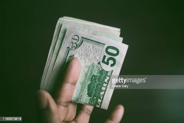close-up of hand holding folded stack of us currency - nota de cinquenta dólares americanos - fotografias e filmes do acervo