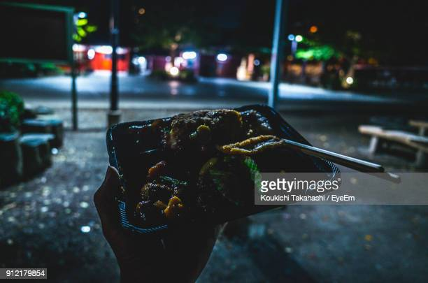 Close-Up Of Hand Holding Food On Street At Night