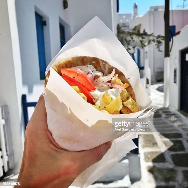 close-up of hand holding food - cyclades islands stock pictures, royalty-free photos & images