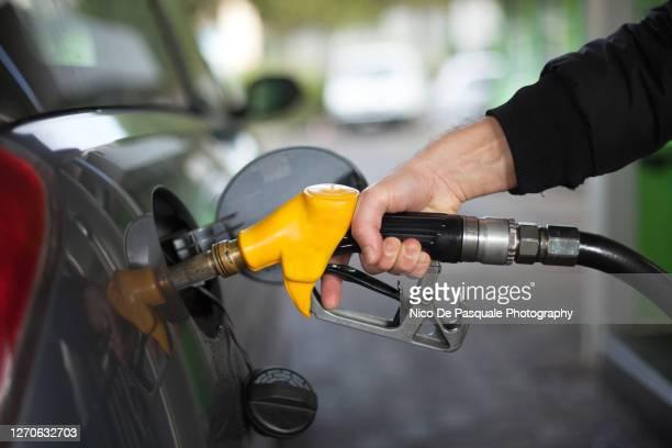 close-up of hand holding fuel nozzle - ガソリン ストックフォトと画像