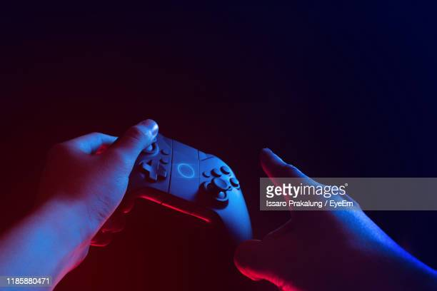 close-up of hand holding game controller against black background - videogiocatore foto e immagini stock