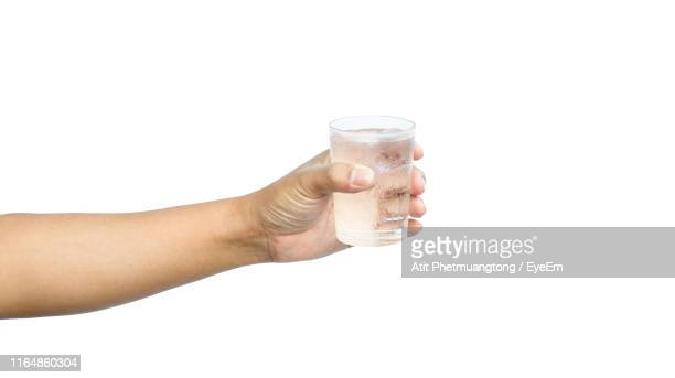 close-up of hand holding glass against white background - verre photos et images de collection