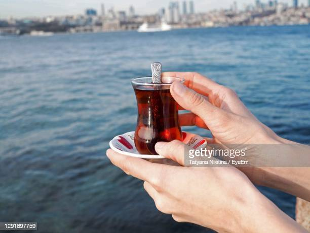 close-up of hand holding glass of tea in turkey istanbul above of sea - nikitina stock pictures, royalty-free photos & images