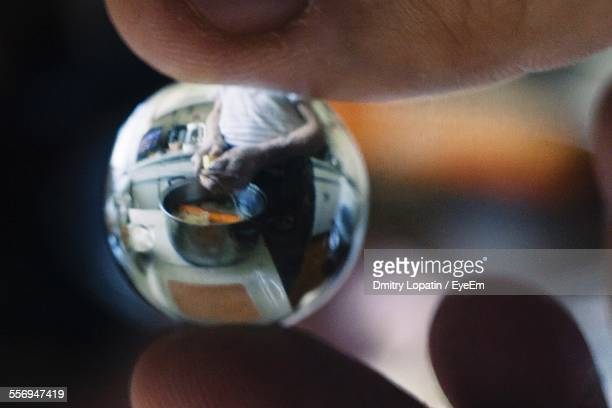 Close-Up Of Hand Holding Glass With Reflection Of Person In Kitchen