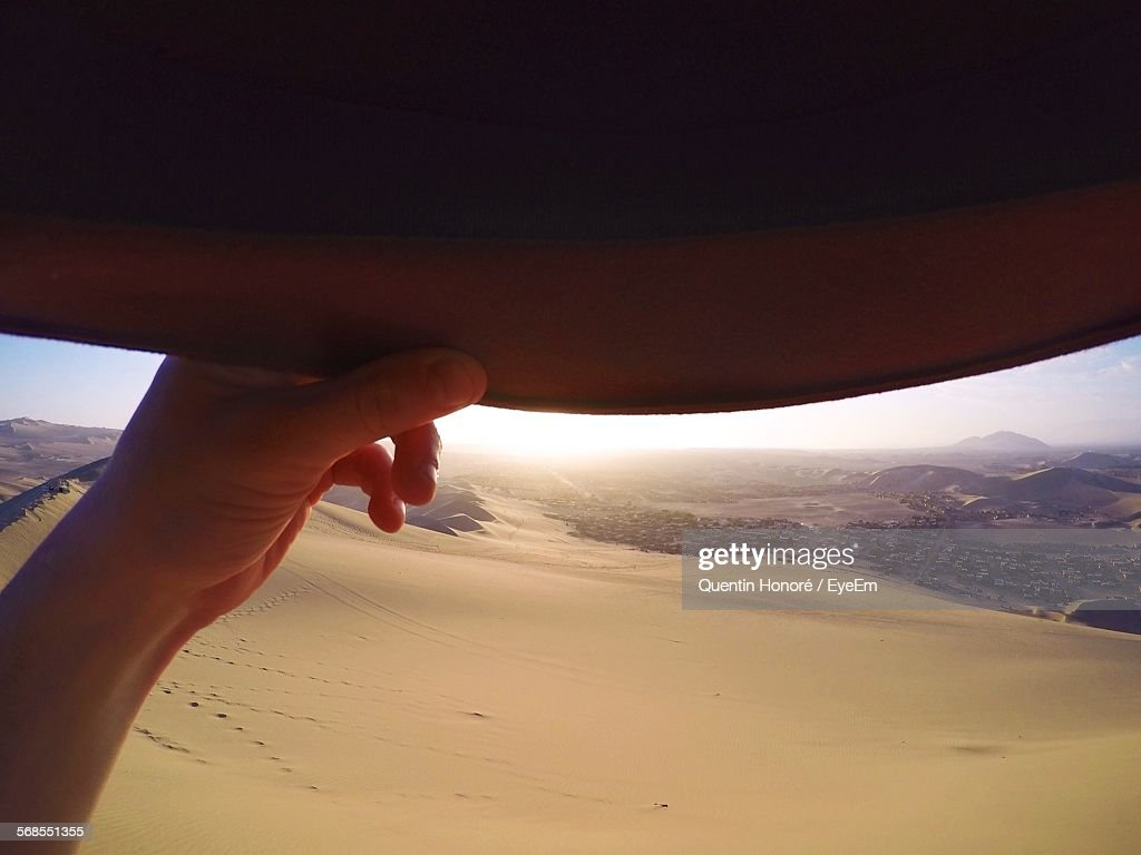 Close-Up Of Hand Holding Hat At Desert : Stock Photo