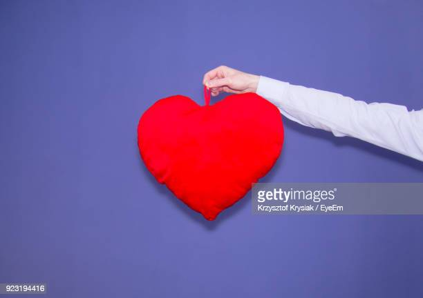 Close-Up Of Hand Holding Heart Shape Against Purple Background
