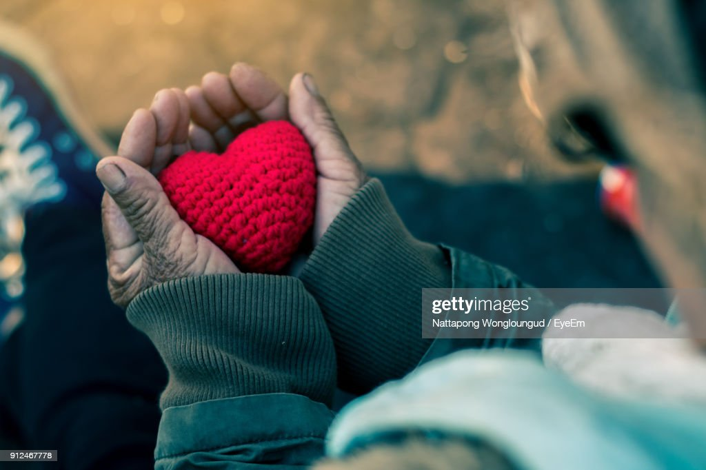 Close-Up Of Hand Holding Heart Shape Knitted Wool : Stock Photo