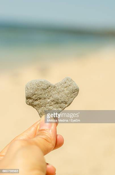 Close-Up Of Hand Holding Heart Shape Stone At Beach