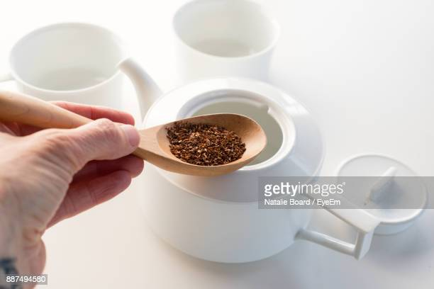 Close-Up Of Hand Holding Herb In Spoon Over Kettle