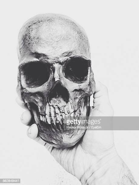 Close-Up Of Hand Holding Human Skull Against White Background