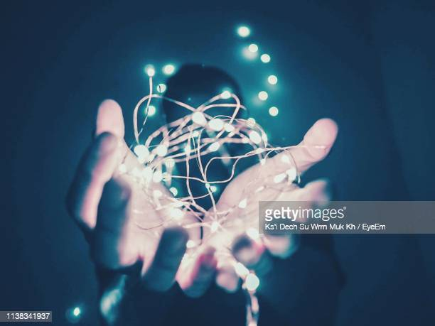 close-up of hand holding illuminated string light - ksi stock photos and pictures