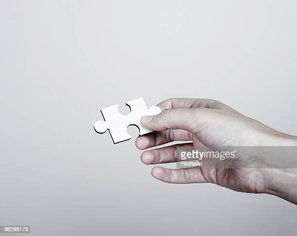 Close-up of hand holding jigsaw piece