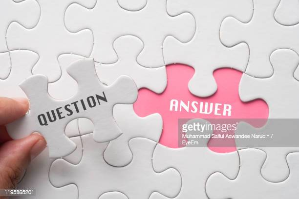 close-up of hand holding jigsaw piece with text - q and a stock pictures, royalty-free photos & images