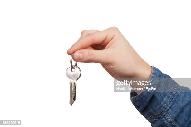 Close-Up Of Hand Holding Key Over White Background