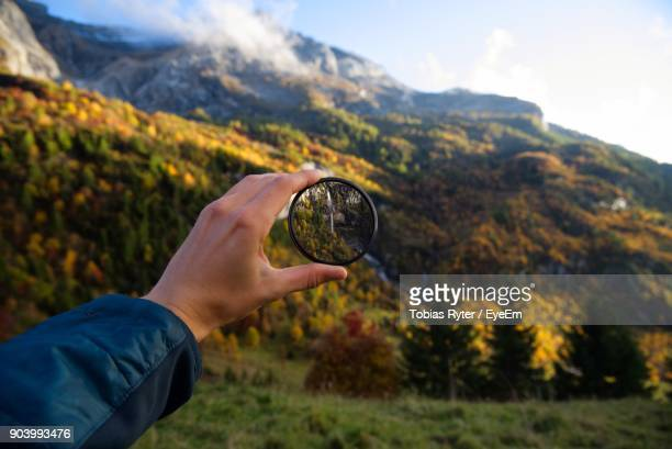 Close-Up Of Hand Holding Lens Against Mountains