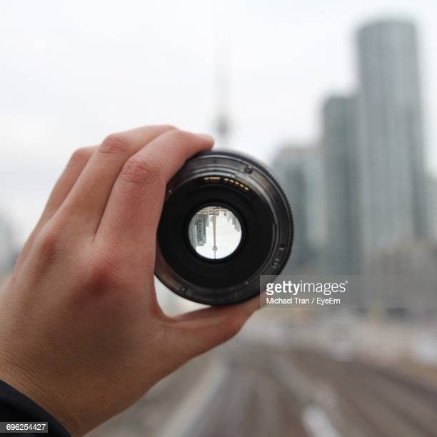 Close-Up Of Hand Holding Lens