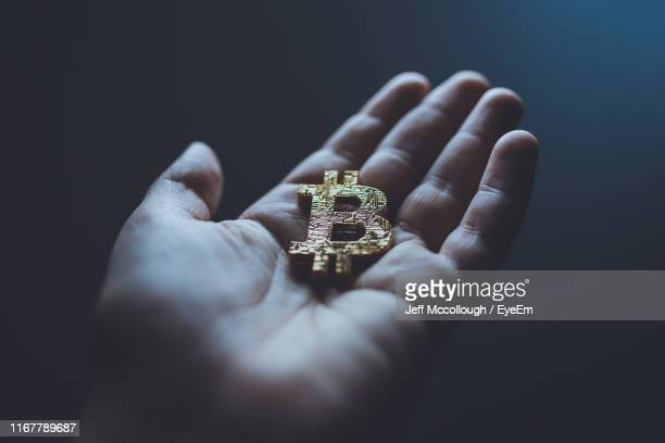 close-up of hand holding letter against black background - crypto monnaie photos et images de collection