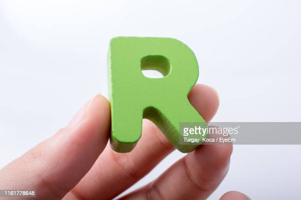 close-up of hand holding letter r against white background - letter r stock pictures, royalty-free photos & images